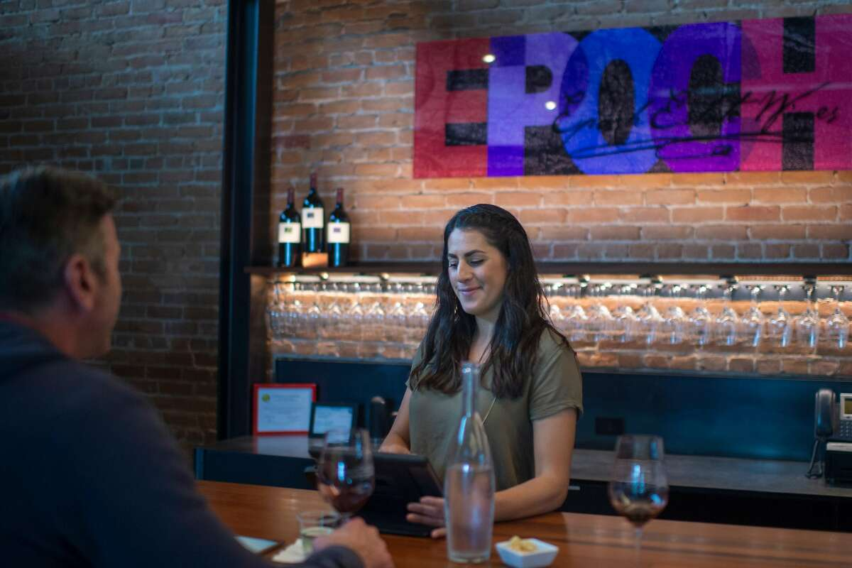 Tasting room educator Stephanie McTiernan, left, pours wine for customers at Epoch Estate Wines in Templeton, Calif.