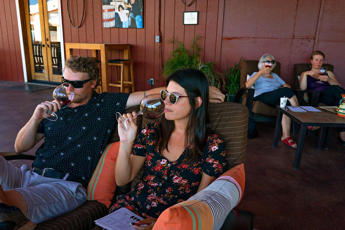 Jessica Juarez and Devon Mullen taste wine at the Papapietro Perry Winery on the deck overlooking the vineyards now that it has reopened its doors. Healdsburg, California on June 18, 2020.