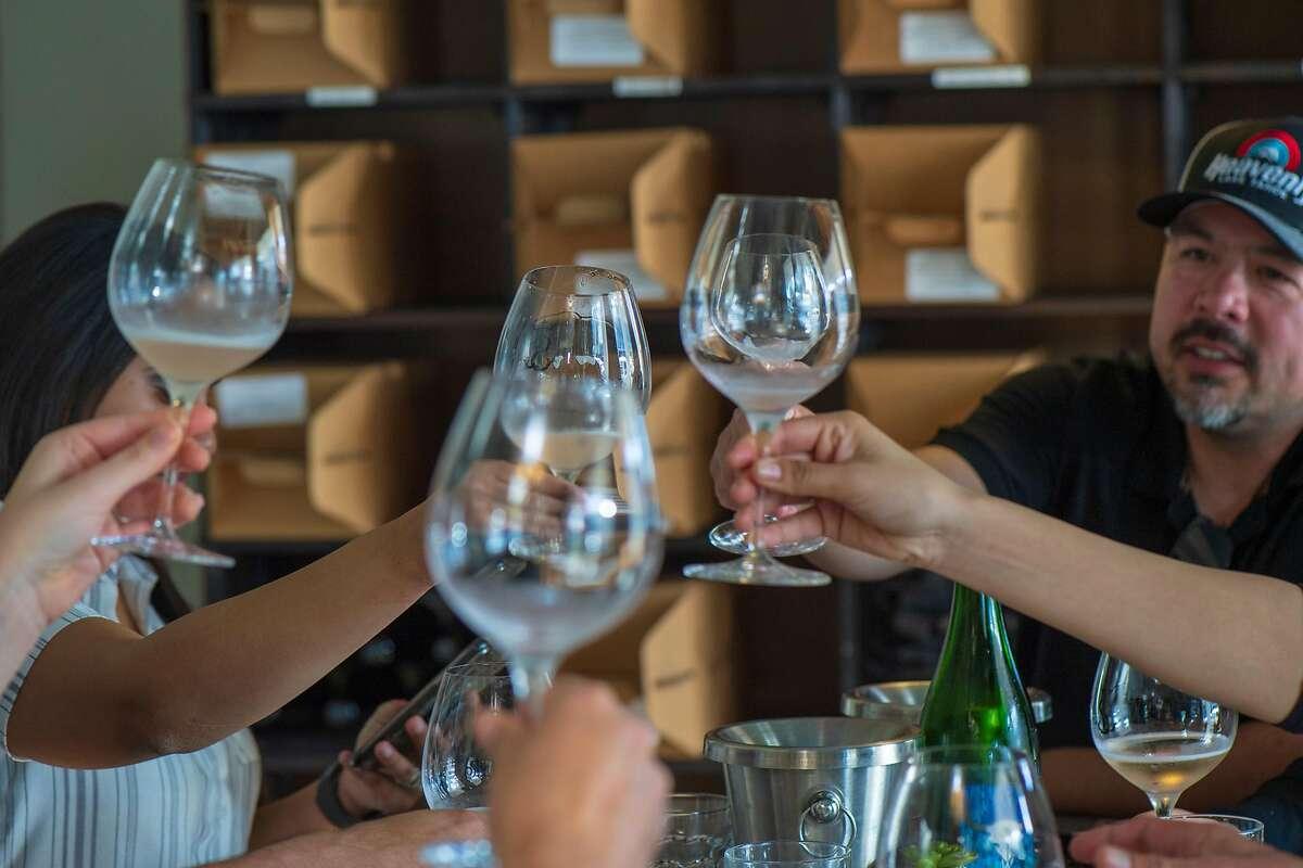 Customer cheers at Sinor-Lavallee tasting room in Avila Beach, Calif.