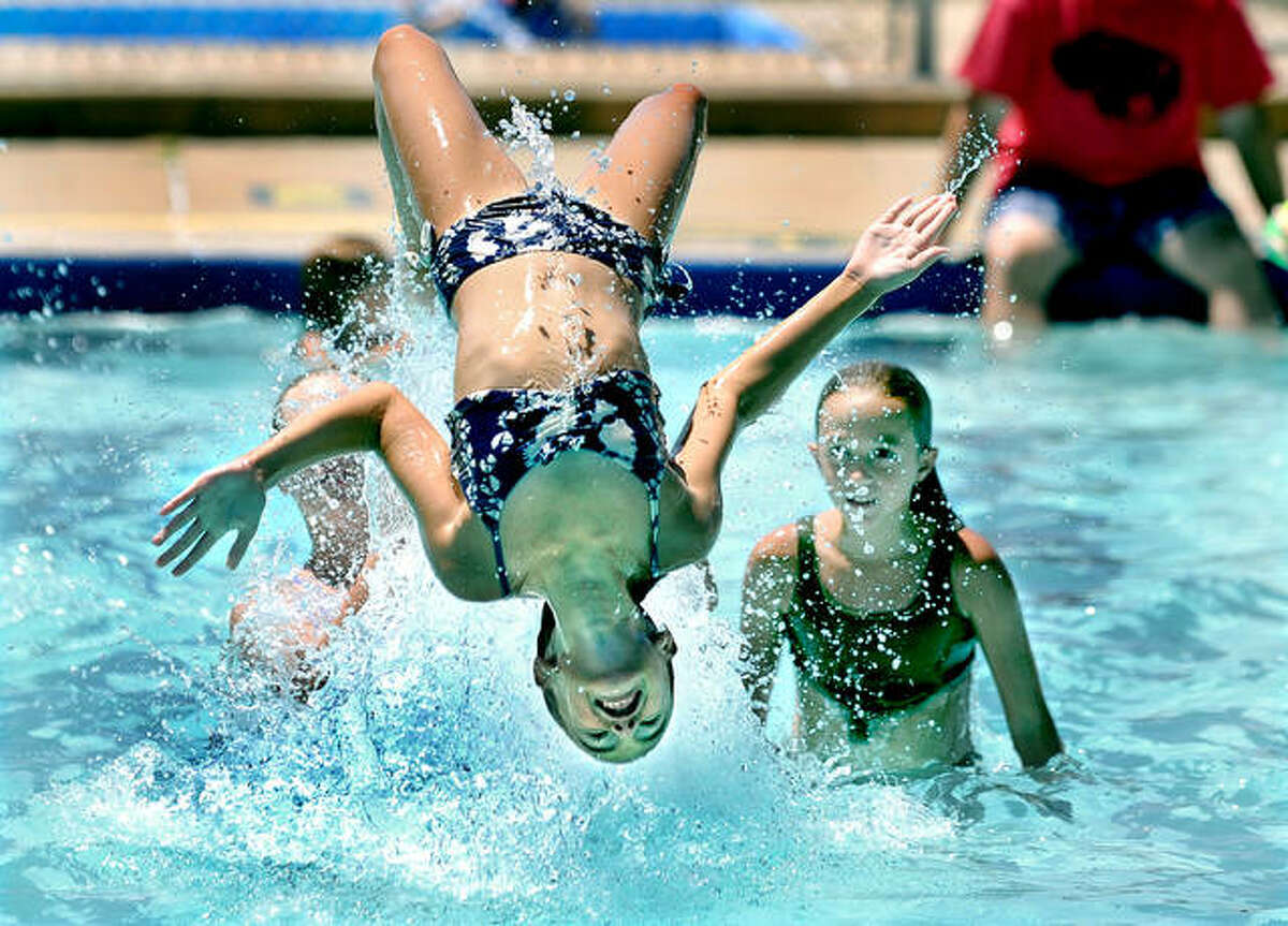 Trying to beat the heat, Scout Jackson, 11, of Edwardsville, backflips in the water with the help of her sister Willow, 10, right, and Parker Levasseur, 12, also of Edwardsville, not pictured, recently at the Montclaire Swim Club in Edwardsville. Through the weekend, the heat will become especially prominent, with temps in the mid-to-upper 90s, according to the National Weather Service.