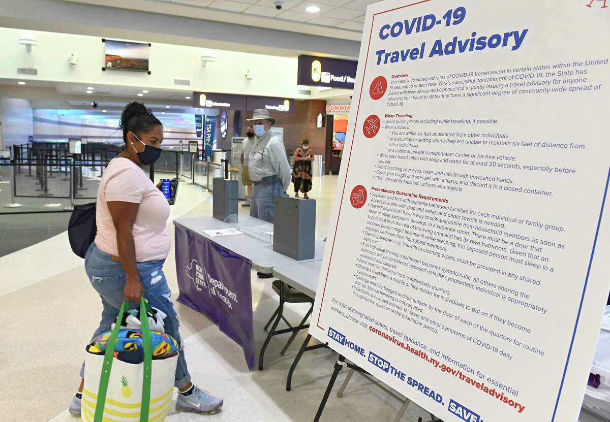 Health Department officials have people fill out forms if they're arriving from Covid hotspot states such as Florida where these passengers came from at the Albany International Airport Tuesday, July 14, 2020 in Colonie, N.Y. (Lori Van Buren/Times Union)