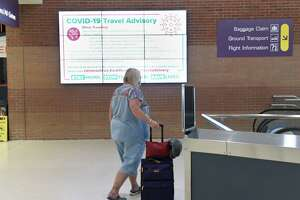 A changing advertisement monitor shows a COVID-19 Travel Advisory at the Albany International Airport Tuesday, July 14, 2020 in Colonie, N.Y. Health Department officials have people fill out forms if they're arriving from Covid hotspot states.(Lori Van Buren/Times Union)