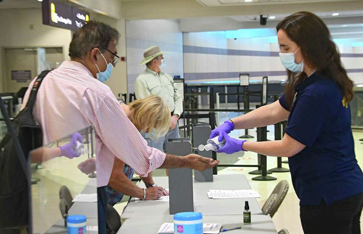 A person working at a New York State Health Department table squirts sanitizer into the hand of a passenger after he filled out a form upon arriving from a a Covid hotspot state at the Albany International Airport Tuesday, July 14, 2020 in Colonie, N.Y. (Lori Van Buren/Times Union)