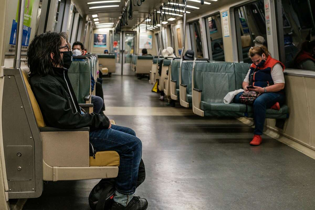 Riders are seen wearing masks on Bart in San Francisco on Wednesday, May 27, 2020.