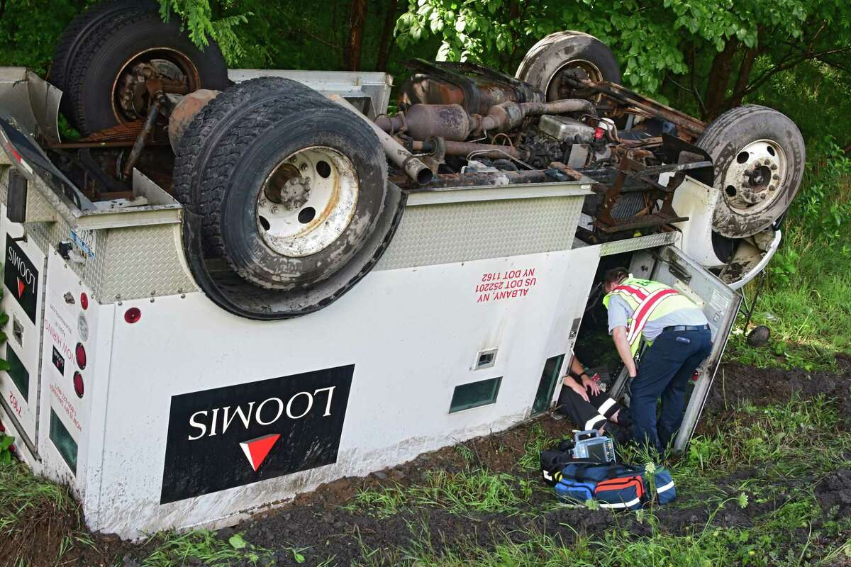 EMT workers check on people inside a Loomis truck which rolled over southbound on I-87 between exit 13 and exit 12 Tuesday, July 14, 2020 in Malta, N.Y. (Lori Van Buren/Times Union)