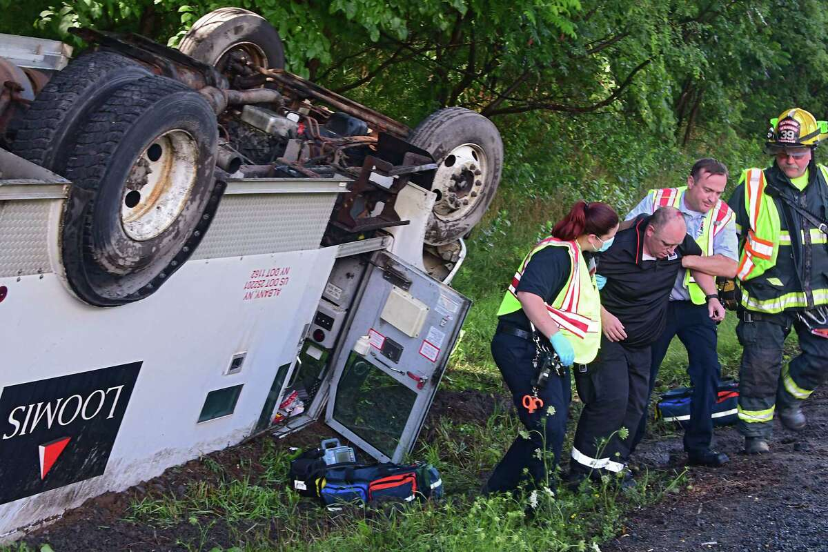 EMT workers and firefighters help a man out of a Loomis truck which rolled over southbound on I-87 between exit 13 and exit 12 Tuesday, July 14, 2020 in Malta, N.Y. (Lori Van Buren/Times Union)