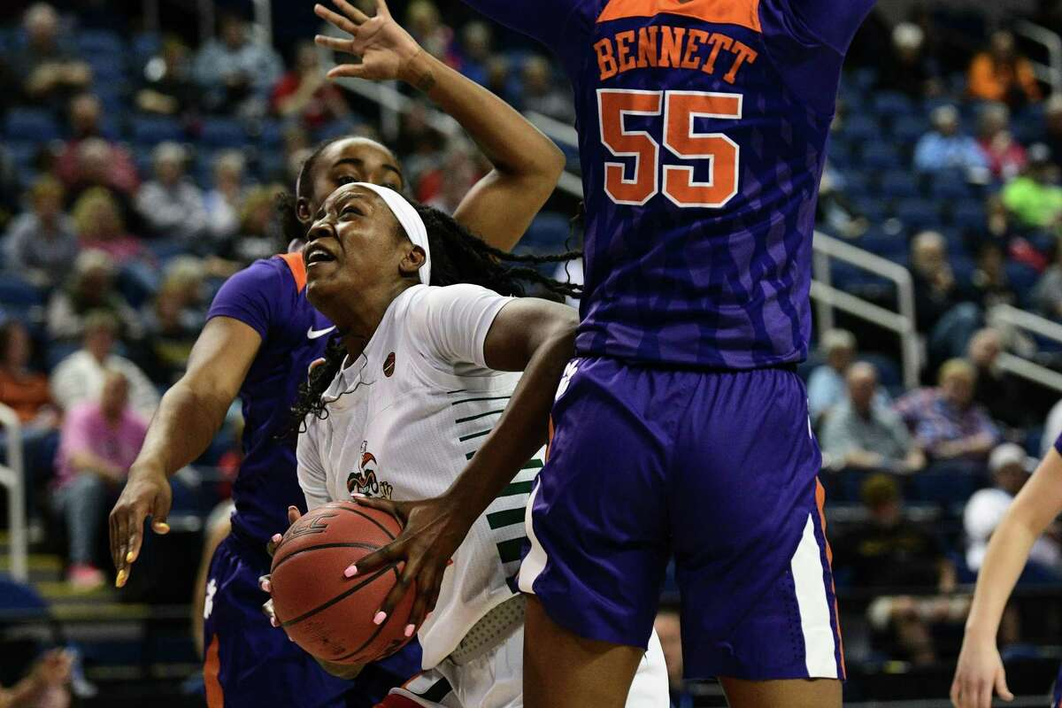 GREENSBORO, NC - MARCH 04: Miami Hurricanes forward Beatrice Mompremier (32) drives between Clemson Tigers center Tylar Bennett (55) and Clemson Tigers guard Chyna Cotton (32) during the ACC Women's Tournament game between the Clemson Tigers and the Miami Hurricanes at Greensboro Coliseum on March 4, 2020 in Greensboro, NC. (Photo by William Howard/Icon Sportswire via Getty Images)