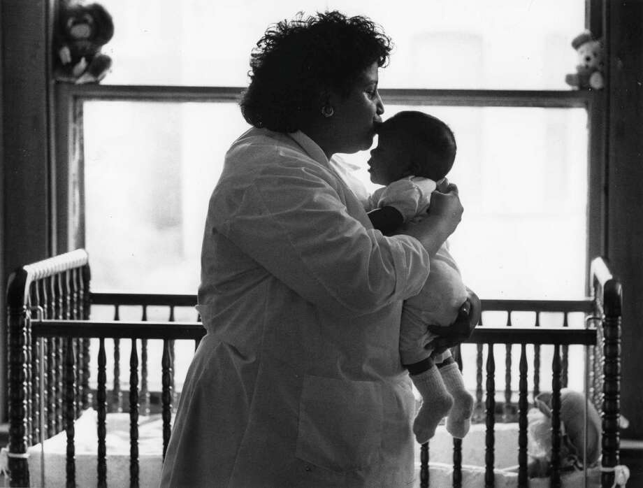 A caretaker cuddles a baby infected with HIV at the nonprofit Grandma's House in the District of Columbia in 1988. The expertise and infrastructure dedicated to finding an HIV vaccine has now pivoted toward coronavirus research. Photo: Washington Post Photo By Frank Johnston / The Washington Post
