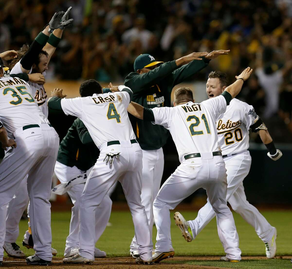 Oakland Athletics' Josh Donaldson (20) is welcomed after hitting the game-winning three-run home run off Baltimore Orioles' Zach Britton in the ninth inning of a baseball game Friday, July 18, 2014, in Oakland, Calif. Oakland won 5-4. (AP Photo/Ben Margot)