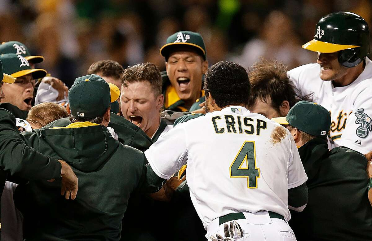 Oakland Athletics' Josh Donaldson, center left, is mobbed by teammates, including Coco Crisp (4), after hitting a game-winning three-run home run off Baltimore Orioles' Zach Britton in the ninth inning of a baseball game Friday, July 18, 2014, in Oakland, Calif. Oakland won 5-4. (AP Photo/Ben Margot)