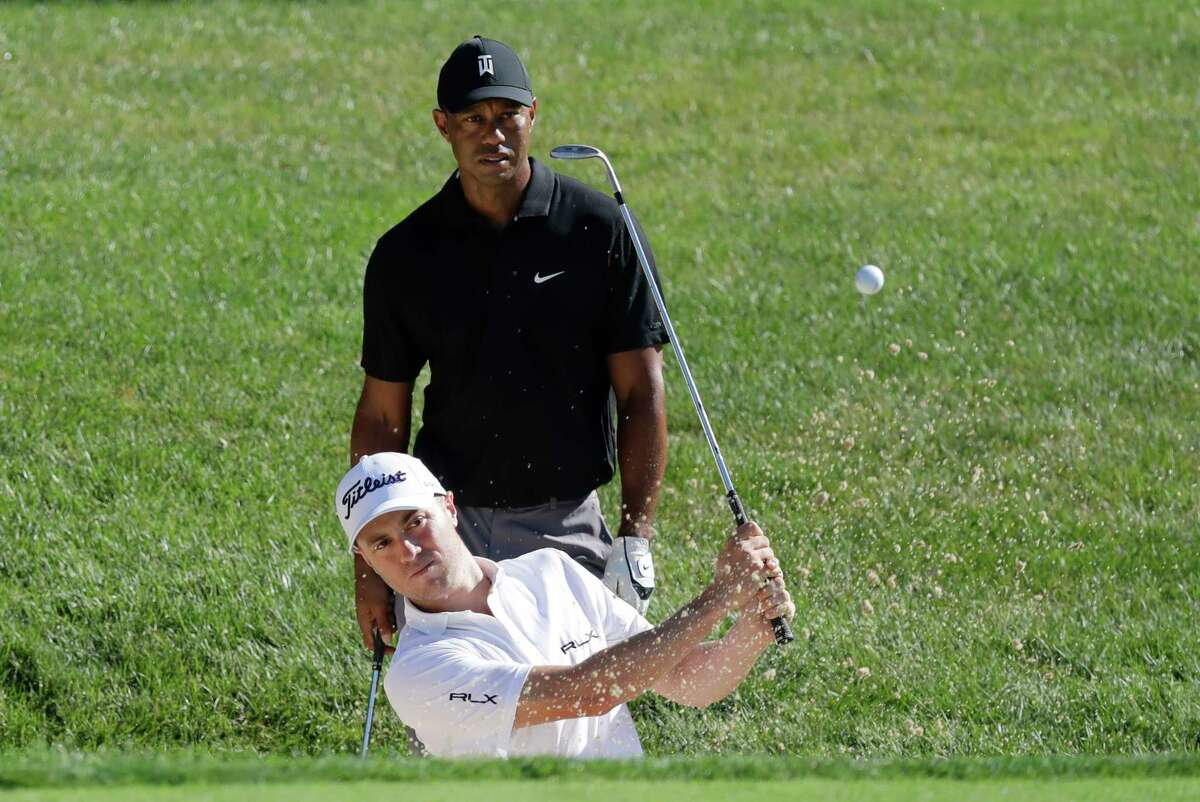 Justin Thomas hits out of a bunker on the 15th hole as Tiger Woods watches during a practice round for the Memorial golf tournament, Tuesday, July 14, 2020, in Dublin, Ohio. (AP Photo/Darron Cummings)