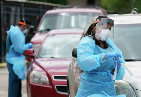 Healthcare personnel work at free COVID-19 testing site conducted by United Memorial Medical Center at the Consulate General Of Mexico, 4506 Caroline St., Sunday, June 28, 2020, in Houston.