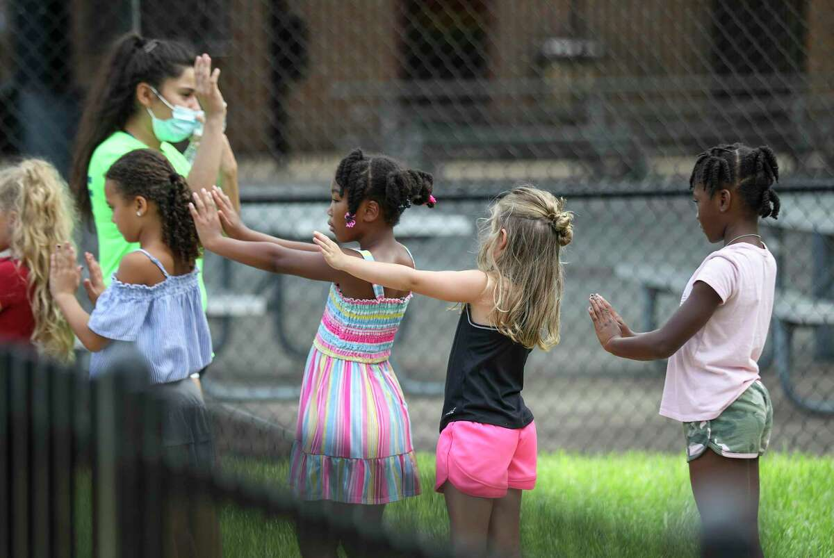 Children line up and practice social distancing as they prepare to go inside Tuesday, July 14, 2020, at the Quillian Center in Houston.