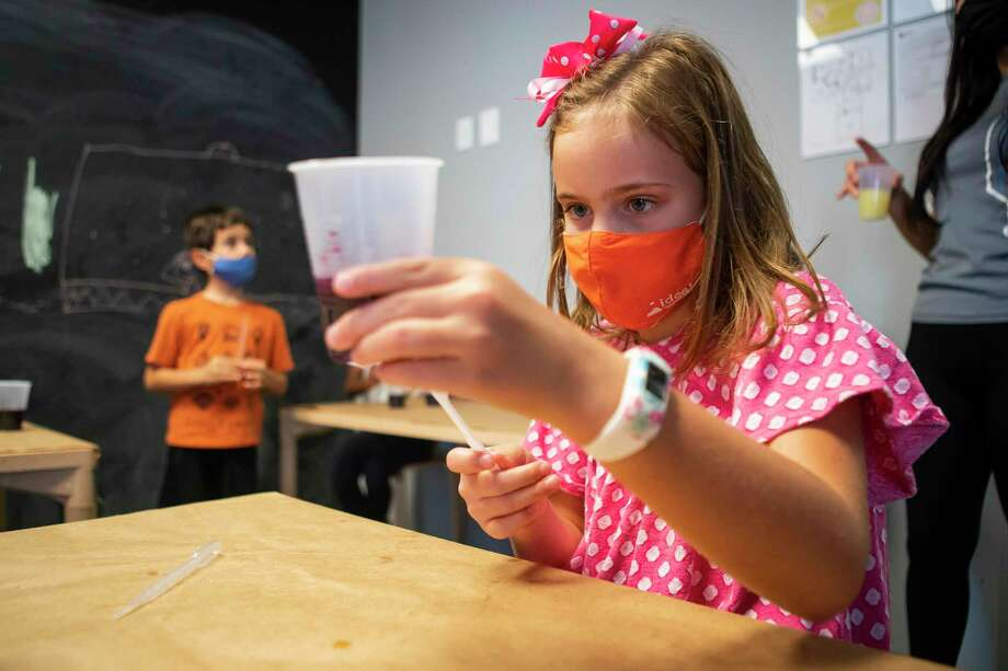 Vivi Varner, 7, works on an experiment with acids and bases during a STEAM summer camp class, Tuesday, July 14, 2020, at IDEA Lab Kids in Bellaire. The business has put numerous protocols into place to try and prevent the spread of COVID-19 between kids, parents and teachers. Check-in each morning happens outside of the business, and temperature checks are made daily as well as requiring masks among the older children and all adults. Photo: Mark Mulligan, Houston Chronicle / Staff Photographer / © 2020 Mark Mulligan / Houston Chronicle