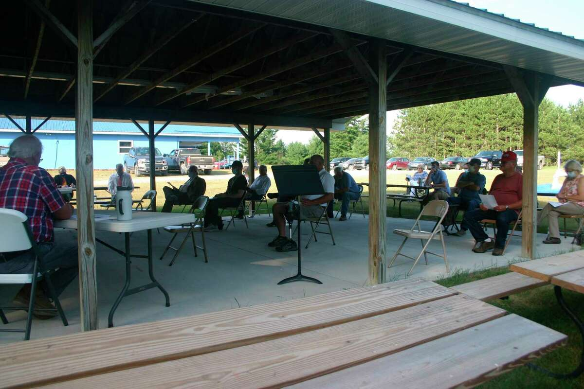 The Evart Township Board of Trustees met outside at the VFW pavilion July 7. It was the first in person meeting since the coronavirus pandemic began. The meeting was held outside to accommodate more public attendance and adhere to social distancing. (Herald Review photo/Cathie Crew)