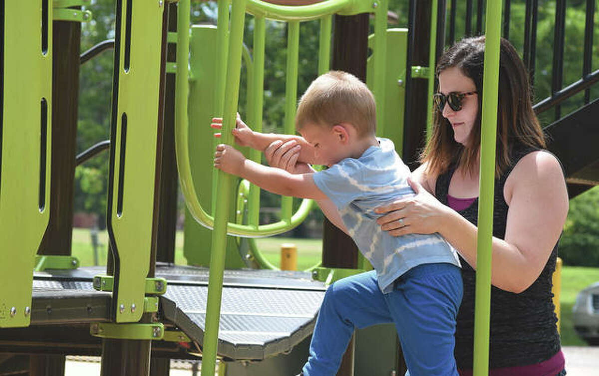 Bennett Shipman, 4, gets help Tuesday from his mother, Makenzie Shipman of Bluffs, while at the playground at Community Park.