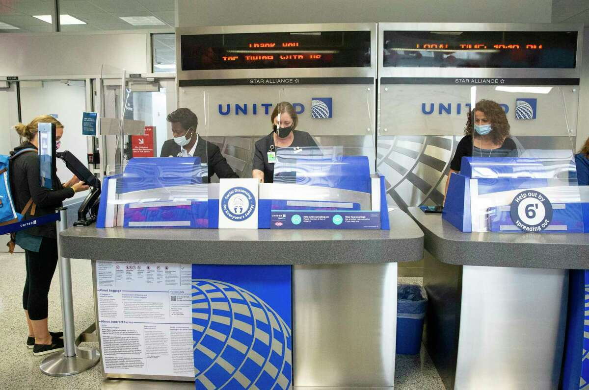 United Airlines customer service representatives help passengers at the boarding gate Tuesday, July 7, 2020, at George Bush Intercontinental Airport in Houston. United Airlines warned it may layoff as many as 3,900 employees at IAH beginning Oct. 1.