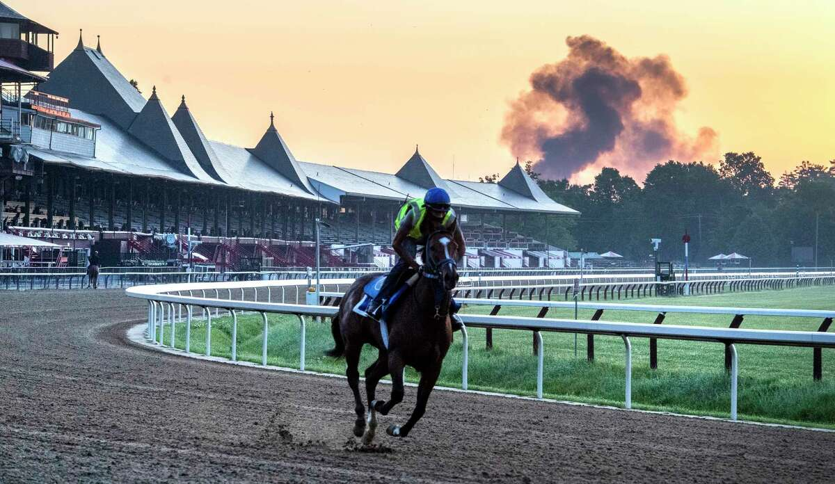 Horses gallop as smoke rises from the area of I-87 in the early morning at Saratoga Race Course July 15, 2020 in Saratoga Springs, N.Y. Photo by Skip Dickstein/Special to the Times Union.