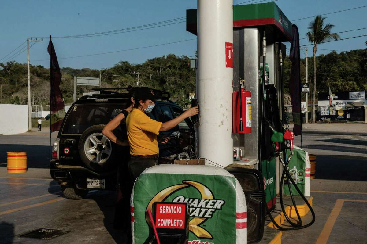 At attendant wearing a protective mask assists a customer at a Pemex gas station in San Francisco, Mexico, on April 22, 2020.