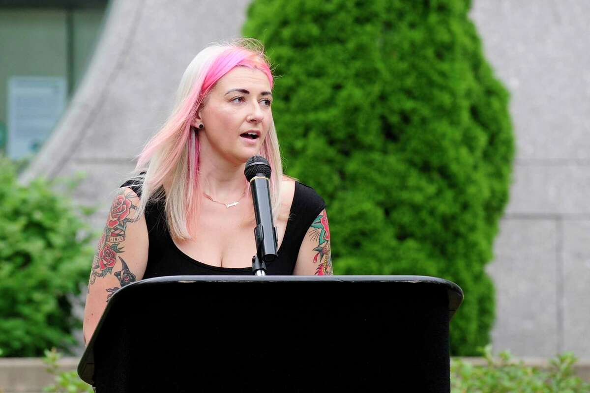 Katie Coelho speaks about her husband, probation officer Jonathan Coelho, during a memorial service outside state Superior Court in Stamford Wednesday. Coelho, who would have been 33 today, died in April after contracting the COVID-19 virus. Below, a portrait of Coelho.
