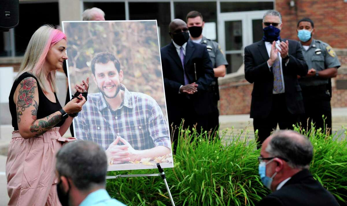 Katie Coelho, of Bethel, passes a portrait of her husband, probation officer Jonathan Coelho, after thanking the attendees of a memorial service outside the Connecticut Superior Courthouse in Stamford, Connecticut on July 15, 2020. Coelho, who would have been 33 Wednesday, died in April after contracting COVID-19. He is survived by his wife, Katie, and his children, Braedyn and Penelope. Several representatives that included various judicial judges, state and local attorneys, courthouse staff, marshals. State, Darien, Stamford and Greenwich Police departments, along with family and friends attended the brief service that honored Coelho.