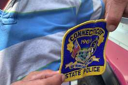 Jay Lynk displays the Connecticut State Police patch given to him in appreciation of his pizza and ice cream lunch for first responders in Derby Tuesday.