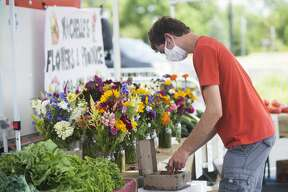 Midland residents peruse stalls at the Midland Area Farmers Market, at its temporary location in the parking lot next to Dow Diamond Wednesday, July 15, 2020. (Katy Kildee/kkildee@mdn.net)