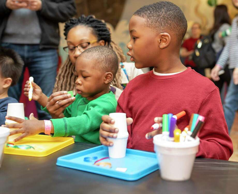 Elijah Mentore watches his brother, Emmanuel Mentore, build a noisemaker at the 9th annual High Noon Countdown event at the Woodlands Children's Museum, Tuesday, Dec. 31, 2019. Photo: Gustavo Huerta, Houston Chronicle / Staff Photographer / Houston Chronicle