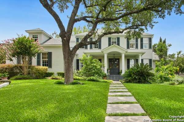 This Terrell Hills beauty emanates elegance with the southern charm of an inviting front porch with rocking chairs lit by gas light fixture and tiled in black slate.