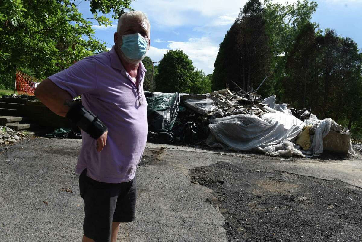 Wayne Holmes stands next to the remains of his home on Wednesday, July 1, 2020, in Albany, N.Y., which was demolished after if caught fire. Holmes is upset with the city's response to the fire, and subsequent demolition. He says he was beaten by police who broke his arm during a confrontation regarding the fire. (Will Waldron/Times Union)