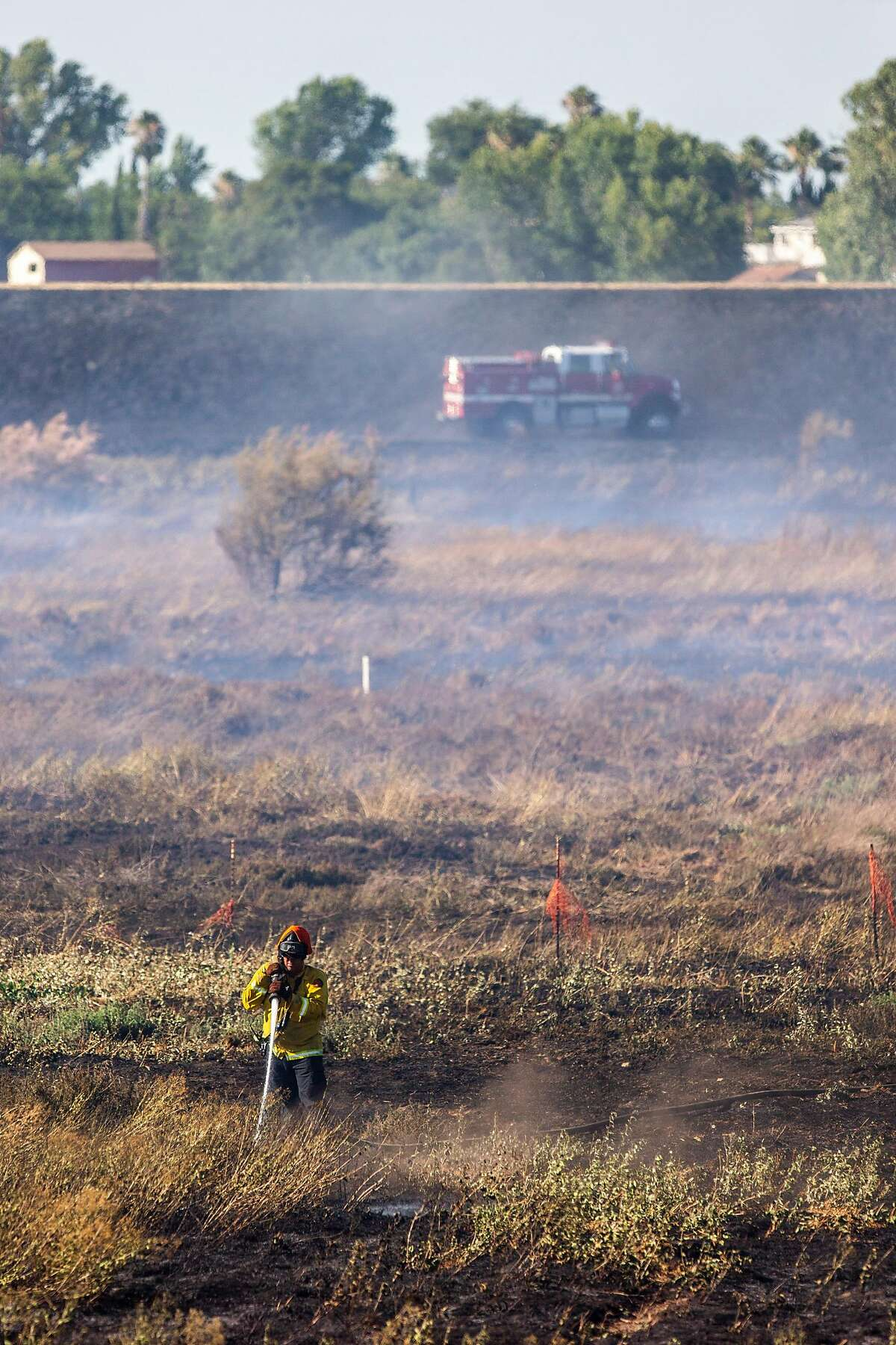 East Contra Costa Fire Protection District puts out a grass fire at E. Cypress Road and Sandmound Boulevard on Tuesday, July 7, 2020, in Oakley, Calif. This is expected to be an intense fire season in California.