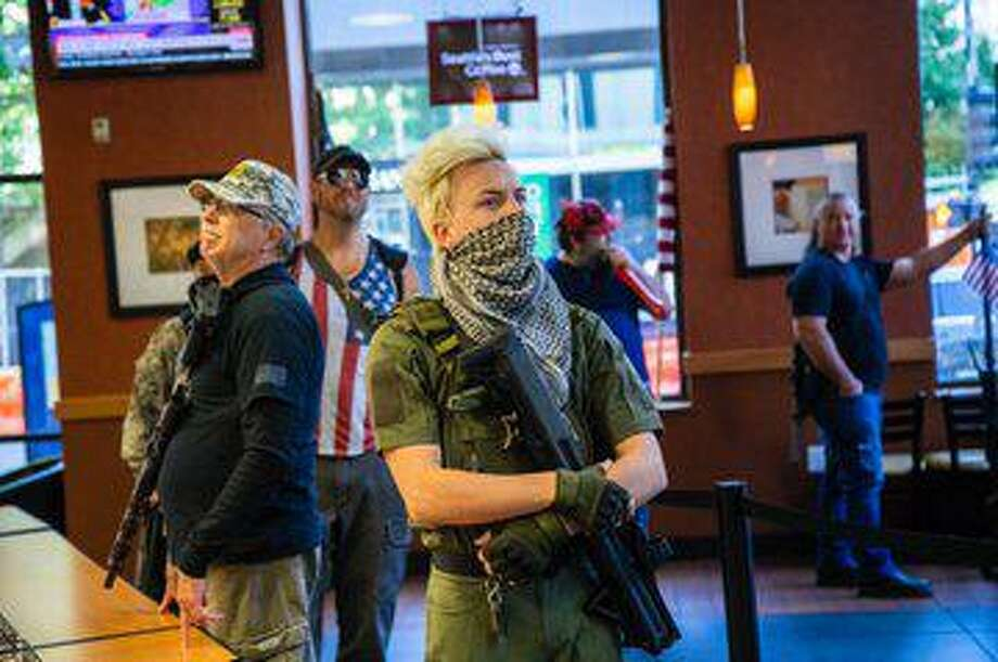 A group of about 11 mostly-armed demonstrators protesting the stay at home order marched around downtown Raleigh May 9 and ordered sandwiches at a Subway. Photo: Travis Long / News & Observer / @vizjourno