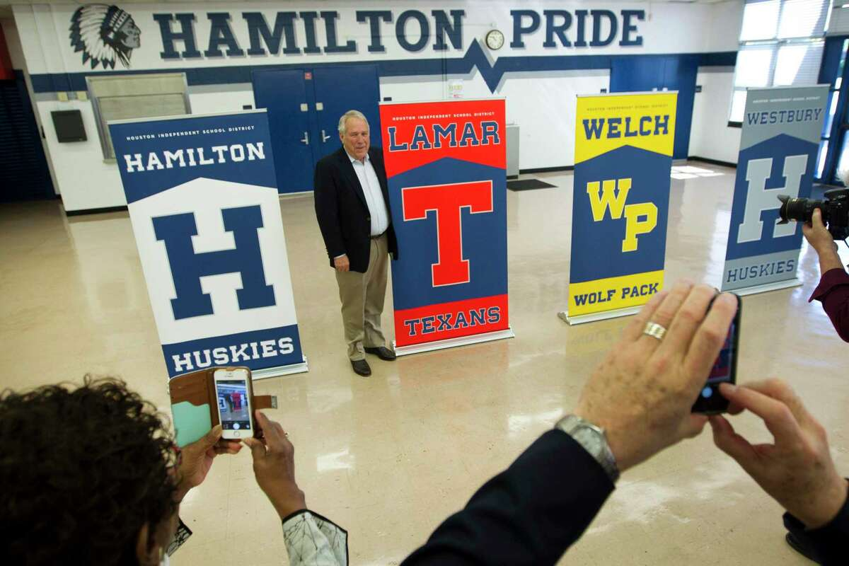 Lamar High School football coach Tom Nolen poses for a photo next to the new mascot names to four schools in the district following a news conference on Tuesday, April 15, 2014, in Houston. HISD announced the new mascots: for Lamar High School, from Redskins to Texans, and Westbury High School, from Rebels to Huskies; Hamilton Middle School, from Indians to Huskies and Welch Middle School, from Warriors to Wolf Pack. ( Brett Coomer / Houston Chronicle )