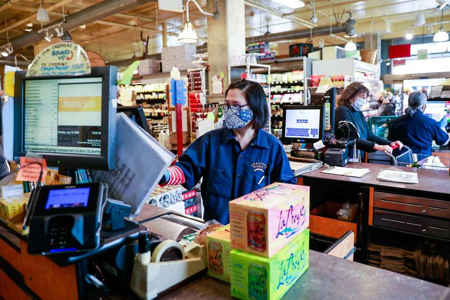 Essential worker Noreen Dosayla checks out a customer at Canyon Market in San Francisco, California on Monday, July 13, 2020. Photo: Gabrielle Lurie / The Chronicle