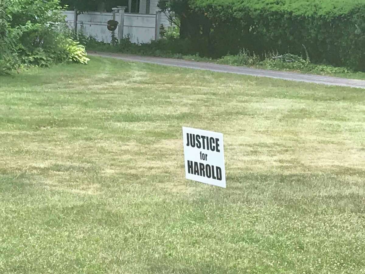 A lawn sign in the village of Kinderhook that's part of a campaign calling for the Columbia County Sheriff's Office to finish the investigation of who assaulted Harold Handy at a July 4th party at a residence in Kinderhook, N.Y. Residents are questioning why the investigation is taking so long.