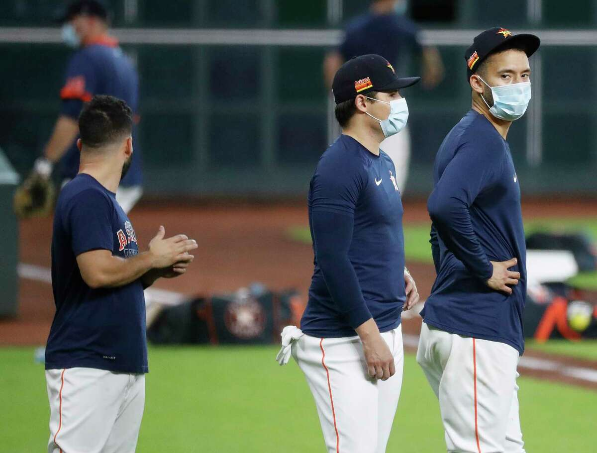 Houston Astros shortstop Carlos Correa wears a mask while practicing base running drills with teammates during the Astros summer camp at Minute Maid Park, Wednesday, July 15, 2020, in Houston.