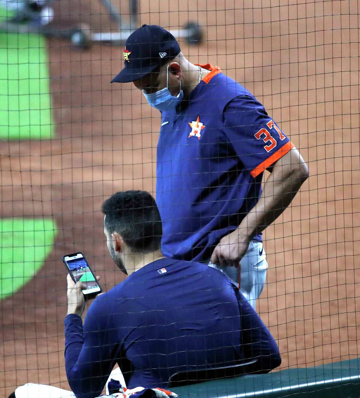 Houston Astros shortstop Carlos Correa looks at hitting coach Alex Cintron's video on his phone during the Astros summer camp at Minute Maid Park, Wednesday, July 15, 2020, in Houston.