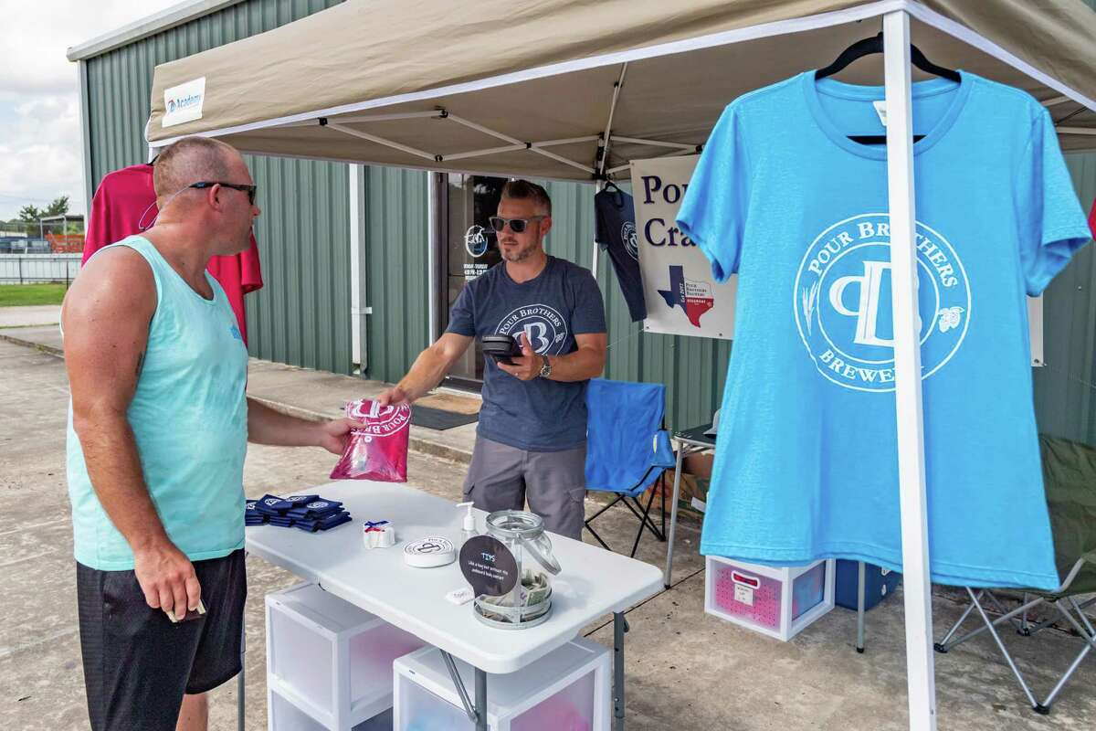 A supporter buys a t-shirt from Nick McLaughlin of Pour Brothers Brewery during the Team 10k Run fundraiser for the brewpub at Crossfit Bridge City on Saturday morning. Photo made on July 11, 2020. Fran Ruchalski/The Enterprise