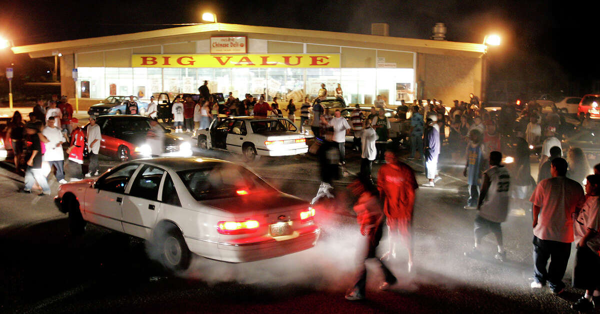 People gather to watch a sideshow at the Big Value parking in south Stockton, Calif., on Sunday, July 16, 2006. The spontaneous nature of the sideshows which are staged on interstates, in deserted parking lots, and on downtown streets keeps police guessing. Departments have spent millions in overtime policing the outlaw rallies.