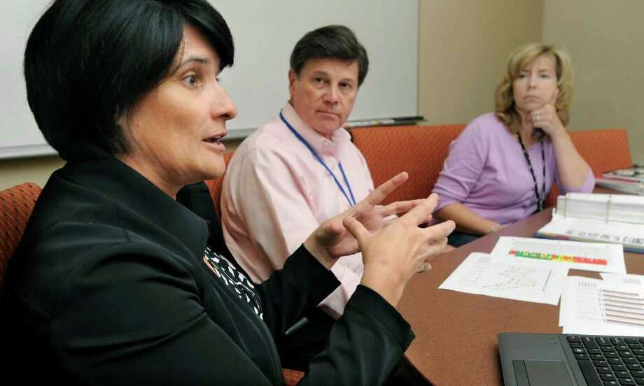 Left to right, Ann Lindenmeyer, administrator of special projects and early childhood, William Glass, deputy superintendent of schools, and Anna Rocco, principal of Ellsworth Avenue Elementary School, discuss test data for Danbury school students. Photo: Carol Kaliff / The News-Times