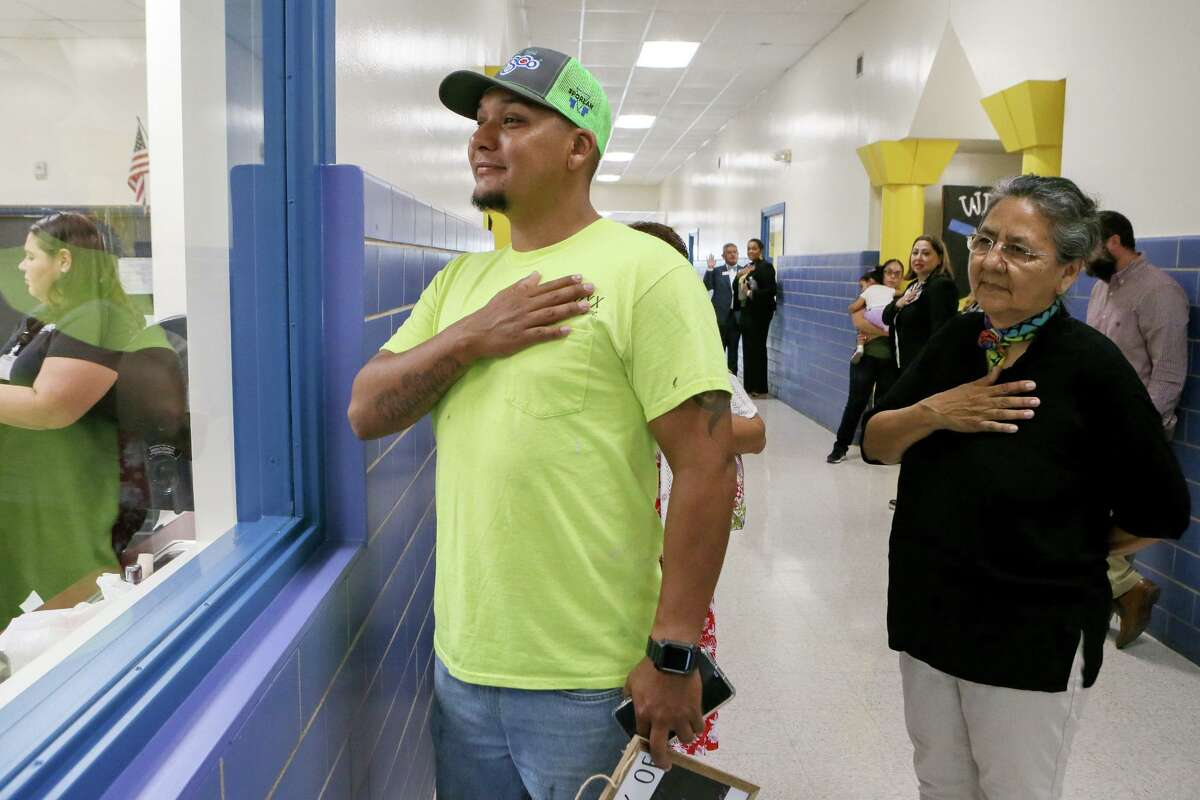 Lorenzo Rodriguez, left, and Gloria Ramirez observe the National Anthem while looking into a kinder classroom on the first day of school at Gardendale Elementary School in 2019. School districts will be allowed to delay reopening this fall due to the coronvirus pandemic if local health authorities order it.