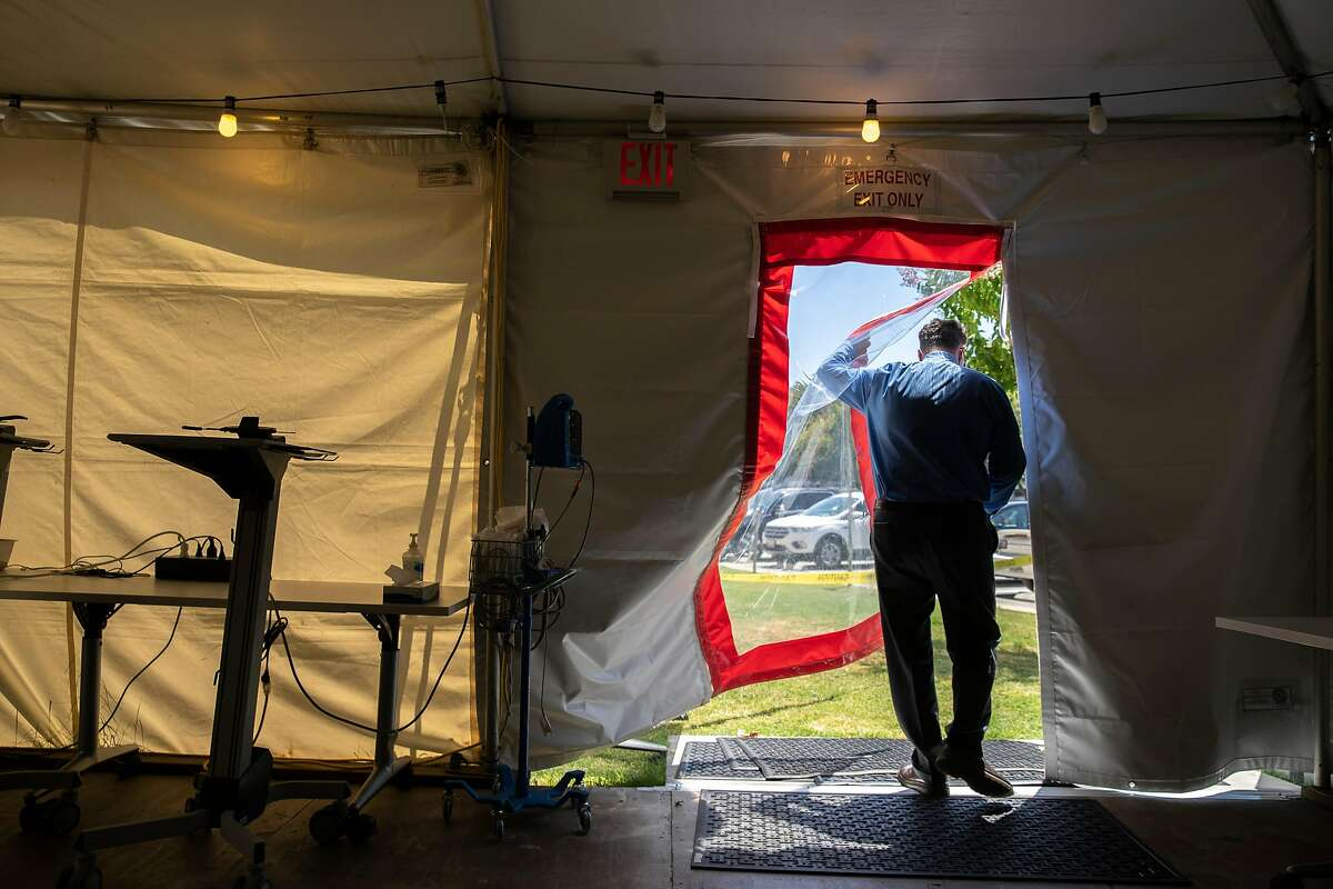 Scott Rocco exits the new hospital tent outside the Santa Rosa Memorial Hospital on Tuesday, July 14, 2020, in Santa Rosa, Calif. Rocco is the nurse manager of the emergency department at Memorial Hospital. Spiking COVID-19 hospitalizations bring fears of the long-awaited coronavirus surge in California. Memorial Hospital put up a tent outside to see patients who don�t need to be hospitalized, but show up with COVID-19 symptoms. The tent is currently being set up and is not in use. The tent would be staffed with two emergency room nurses and one emergency room doctor and has a capacity to see up to six patients at a time.