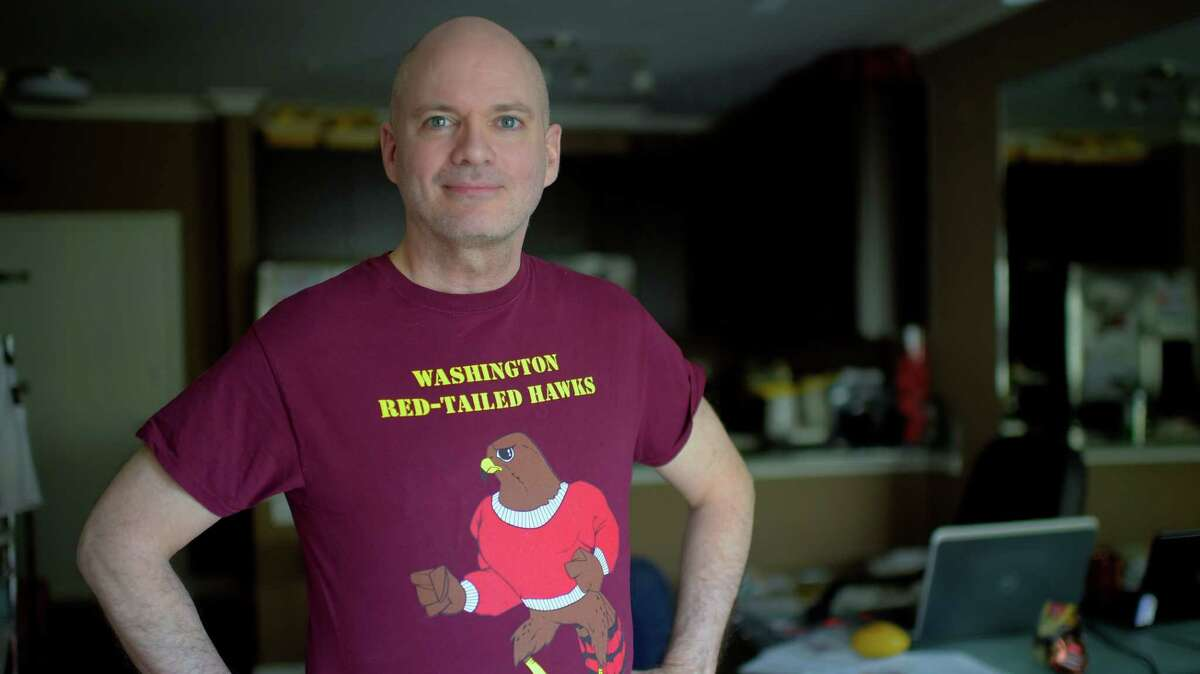 """Martin McCaulay wears a """"Washington Red-Tailed Hawks"""" T-shirt while posing for a photograph in 2015."""