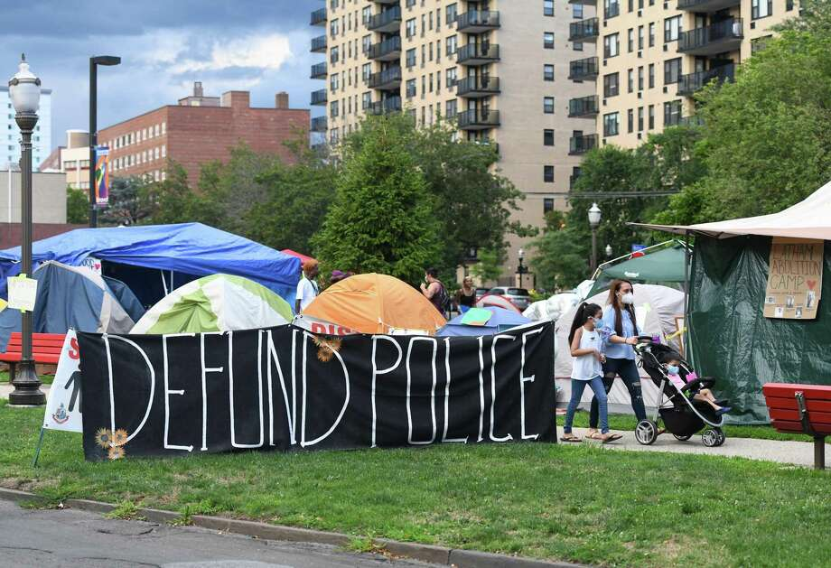 """A large """"defund police"""" sign is displayed outside the Latham Abolition Camp at Latham Park in Stamford, Conn. Tuesday, July 14, 2020. A group of protestors has been camped out at Latham Park since the weekend protesting the death of Steven Barrier, who died in police custody in October of 2019, and demanding reform from the local police department. Photo: Tyler Sizemore / Hearst Connecticut Media / Greenwich Time"""