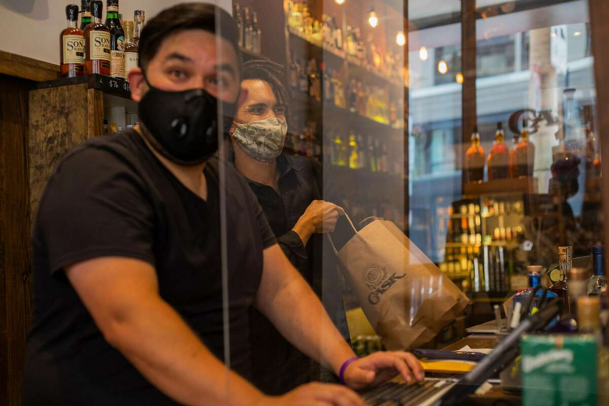 CASK employees Greg Yang, left, and Cody Updegrave, right, help a customer check out on Wednesday afternoon in downtown San Francisco, CA on July 15, 2020.