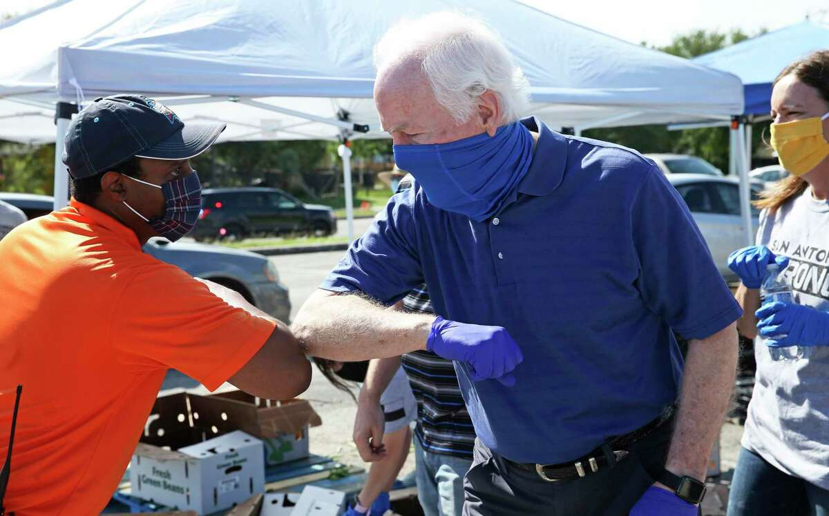 Senator John Cornyn greets with elbow bumps as he helps the Food Bank distribute groceries at the Alamodome on May 29, 2020.