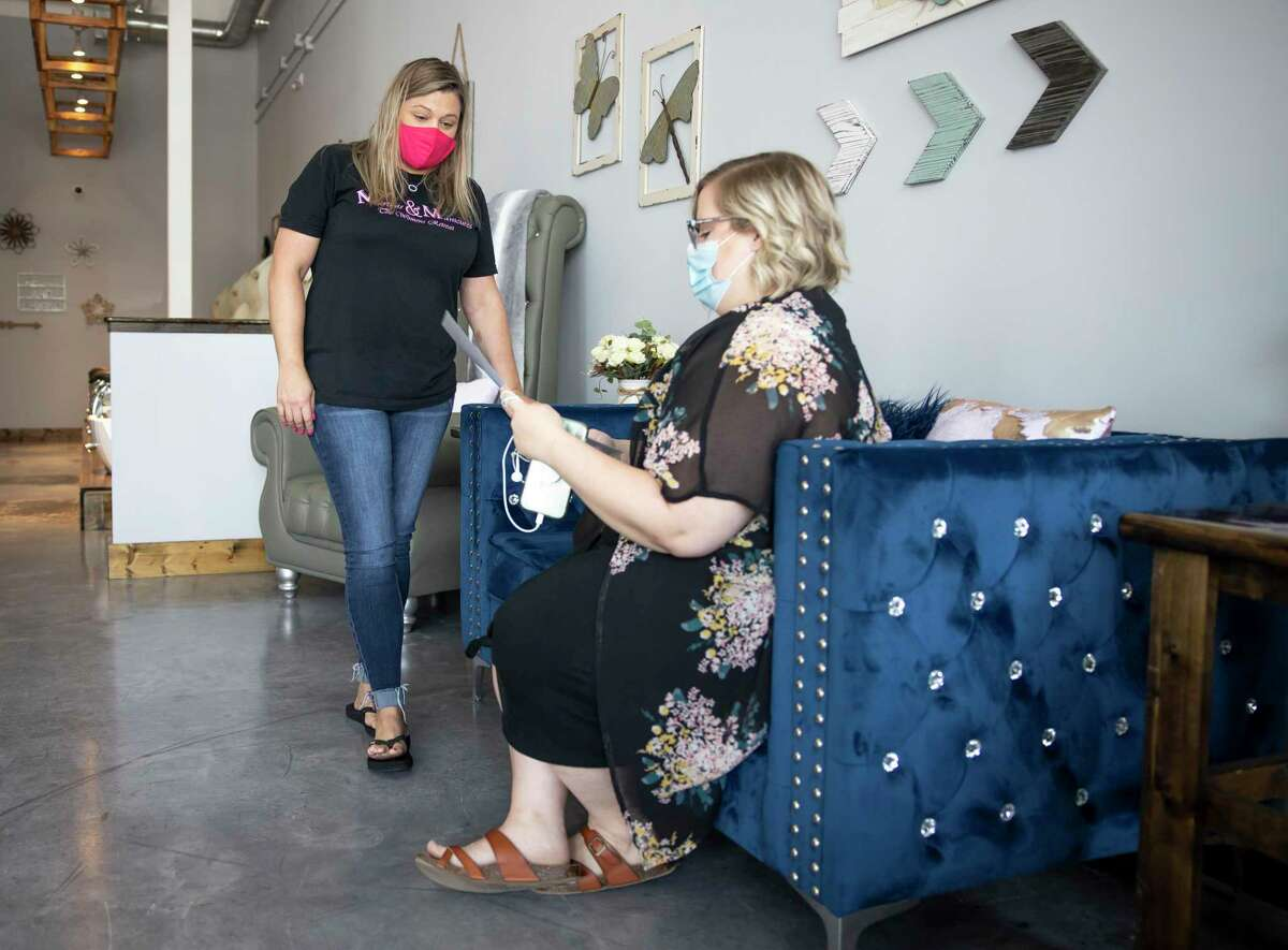 Keri Strokes, manager at Martinis & Manicure, offers Caitlyn Jones a drink in Shenandoah, Thursday, July 9, 2020.The business has been trying to follow state regulations for cosmetology businesses and Governor Greg Abbott's order.