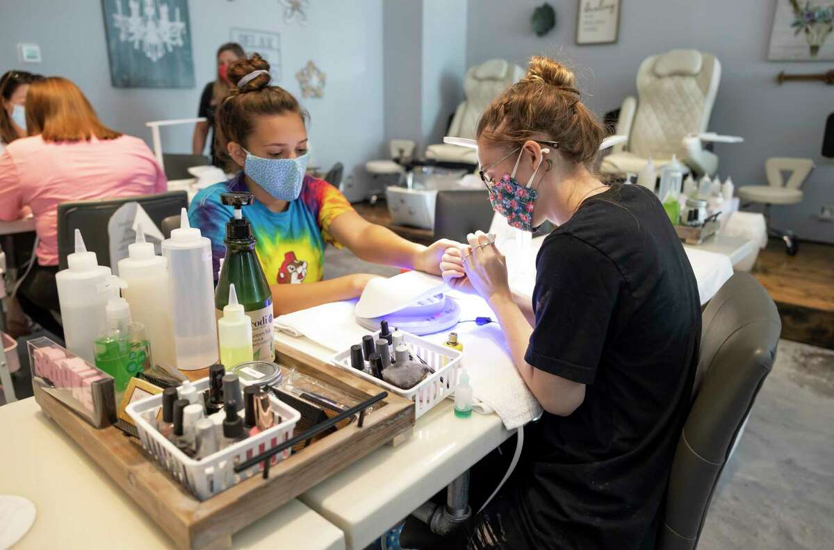 Sarah Claramunt, right, gives Reese Alewine, left, a manicure at Martinis & Manicure in Shenandoah, Thursday, July 9, 2020.The business has been trying to follow state regulations for cosmetology businesses and Governor Greg Abbott's order.