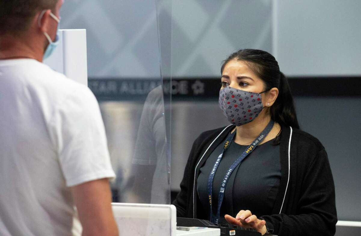 A United Airlines customer service representative helps a passenger at check-in counter from behind plastic plates-one of the ways to protect customers and employees-Tuesday, July 7, 2020, at George Bush Intercontinental Airpo in Houston.
