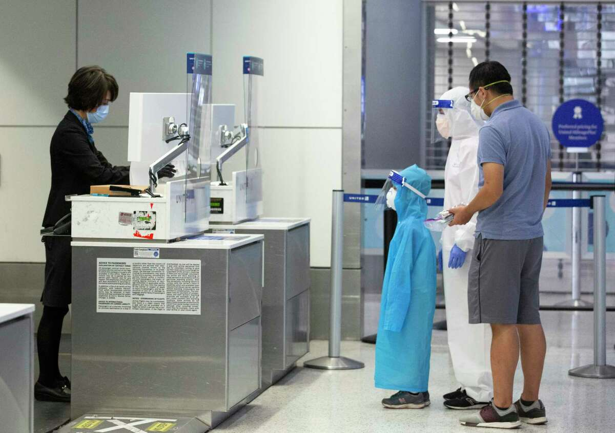 A United Airlines customer service representative helps passengers at check-in counter from behind plastic plates-one of the ways to protect customers and employees-Tuesday, July 7, 2020, at George Bush Intercontinental Airport in Houston.